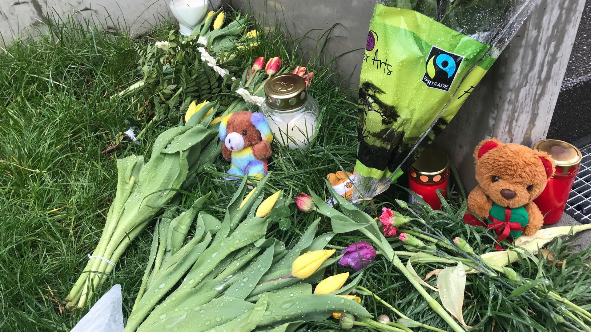 Blumen, Kerzen und Teddybären liegen im Gras