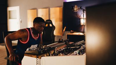 Ein junger Mann sitzt in einem Musikstudio an den Reglern, im Hintergrund ist ein Mikrofon zu sehen.