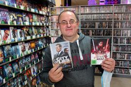 ein Mann steht in einer Videothek und hält DVDs hoch