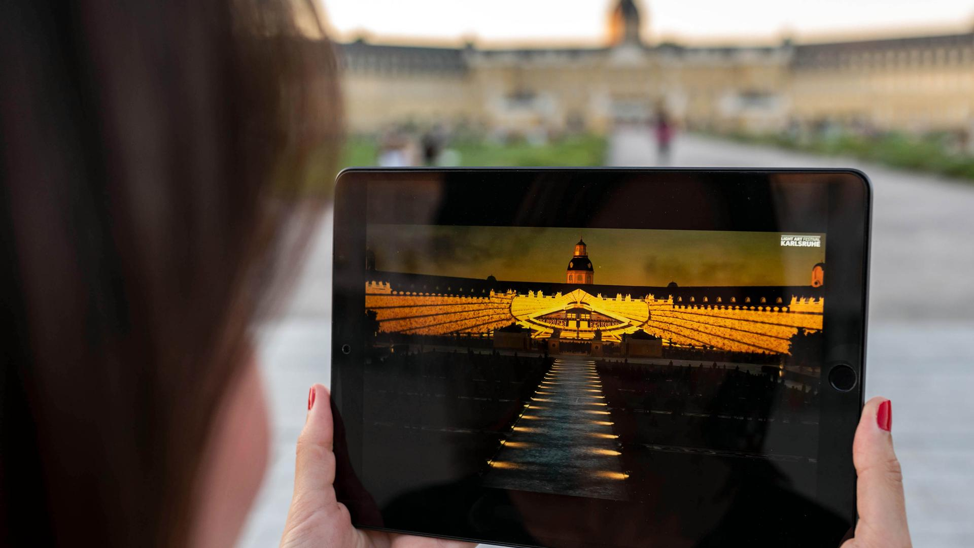 Vor dem Schloss Karlsruhe betrachtet eine Person auf einem Tablet einen Teil der Schlosslichtspiele, die 2020 wegen der Corona-Pandemie virtuell im Internet stattfinden mussten.