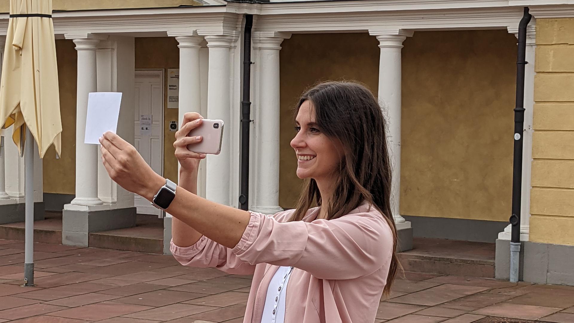 Eine junge Frau hebt vor dem Karlsruher Schloss ein ausgedrucktes Bild hoch und macht ein Foto davon.