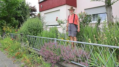 Axel Plitt steht in seinem Wildblumen-Garten in Karlsruhe. Einige Pflanzen ragen über Mauer und Zaun hinaus auf den Gehweg.