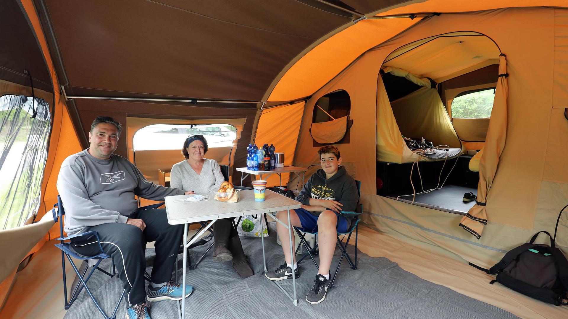 Christian, Melissa und Benjamin Blanke (von links) sitzen im Zelt vor ihrem neuen Faltcaravan.