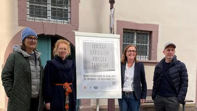 Vier Personen vor Plakat