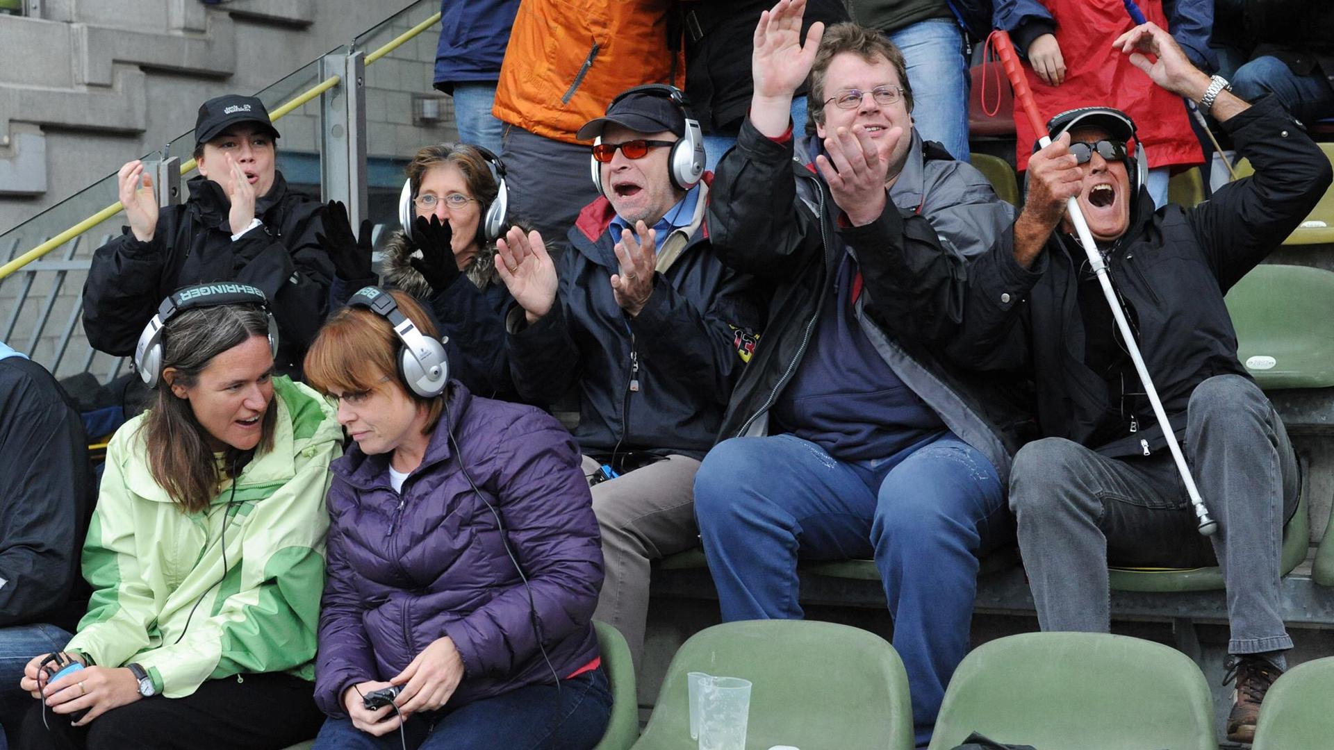 Fußball-Fans im Stadion mit Kopfhörern und Blindenstock.