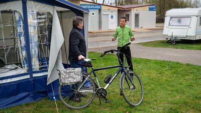 10.4.2021 Betriebsleiter Rocco Trunz, Campingplatz Durlach, mit einem Gast aus Nordrhein-Westfalen, der mit seinem Fahrrad am Vorzelt seines Wohnwagens steht