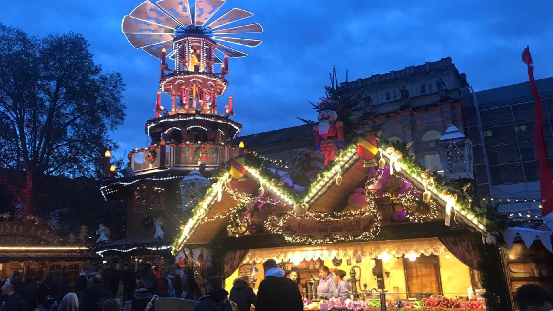 Die Glühwein-Pyramide auf dem Karlsruher Weihnachtsmarkt im Hintergrund, vorne ein Süßigkeiten-Stand.