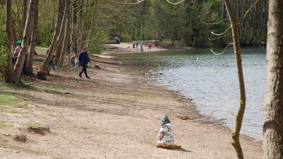 Menschen stehen im Frühjahr am Ufer des Baggersees Grötzingen.