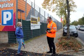 Bernhard Enderlin vom Tiefbauamt Karlsruhe erklärt Elke Stiefel in Grünwinkel, wer die Gehwege und Rinnsteine bei Firmengebäuden sauber hält.
