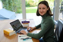 Johanna Gring sitzt zuhause vor ihrem Laptop. Daneben liegen ein Notizblock mit Stiften und Wörterbücher.