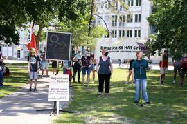 """Protest in der Innenstadt: Rund 70 Interessierte lauschten am Samstag auf dem Friedrichsplatz der Kundgebung der Initiative """"Perspektive aus der Krise"""". An einem Mikrofon steht eine junge Frau und spricht. Dahinter sind Menschen mit Mundschutz und Bannern, die zuhören."""