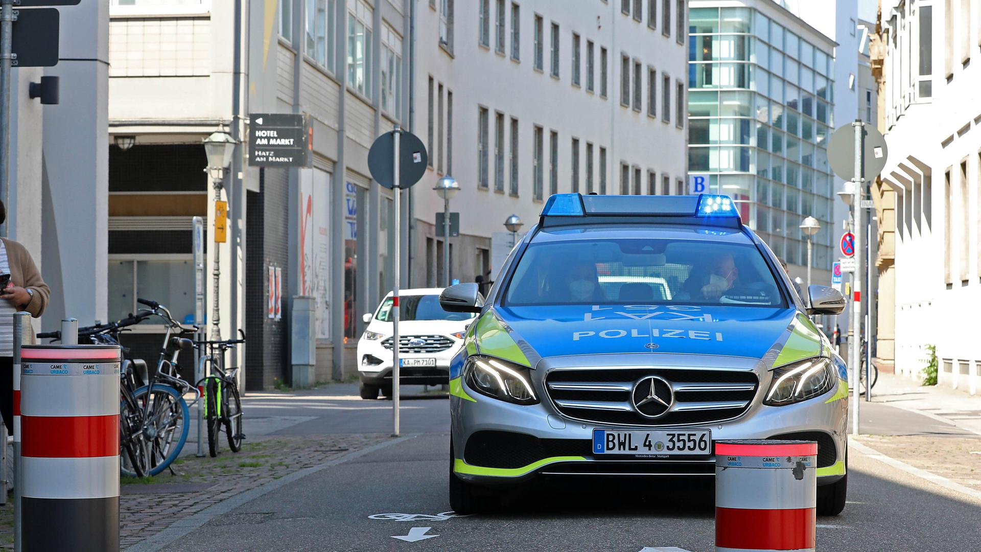 Ein Streifenwagen der Polizei nähert sich dem versenkbaren Poller im Zirkel.