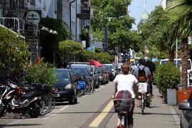 Viele Radfahrer und einige Fußgänger durchqueren die Südliche Waldstraße.