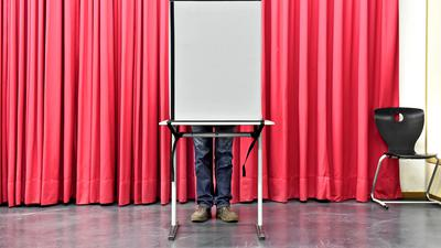 Ein Mann gibt im Wahllokal Goethe-Gymnasium in Karlsruhe bei der OB-Wahl seine Stimme ab.