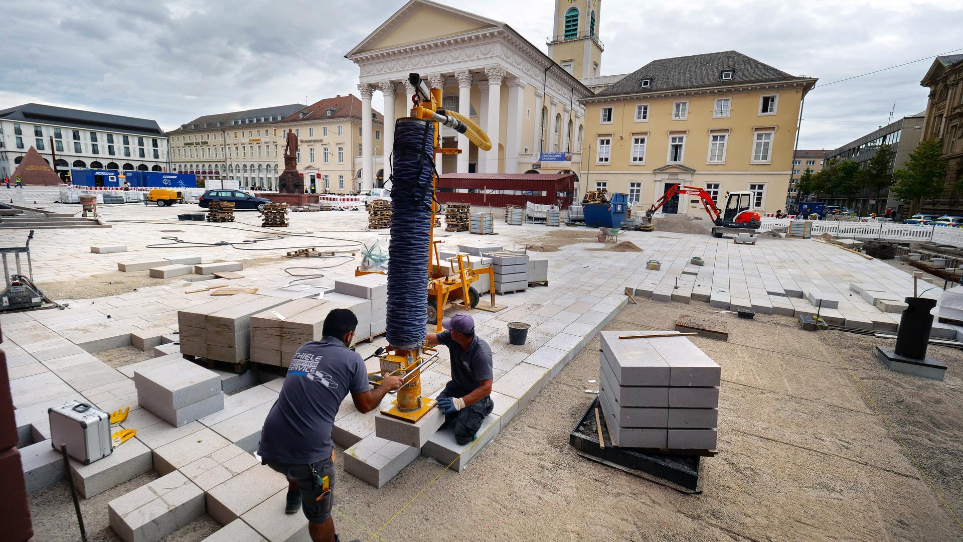 Auf den letzten Quadratmetern: Das neue Pflaster des Marktplatzes schließt sich. Die Arbeiter fügen die fehlenden Granitsteinplatten in der Südwestecke der guten Stube ein.
