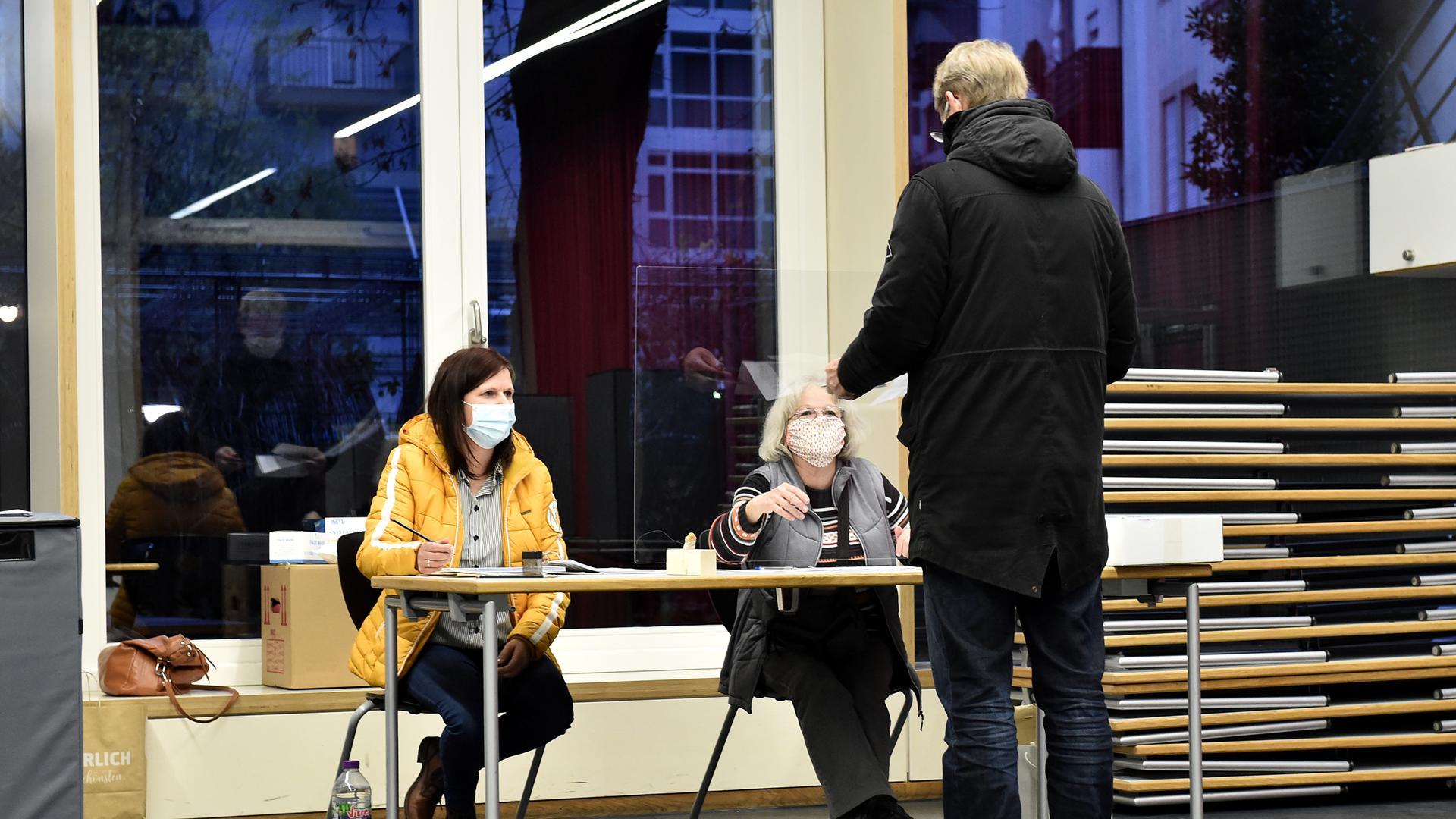 Ein Mann gibt bei der OB-Wahl in Karlsruhe im Wahllokal Goethe-Gymnasium seinen Stimmzettel ab.