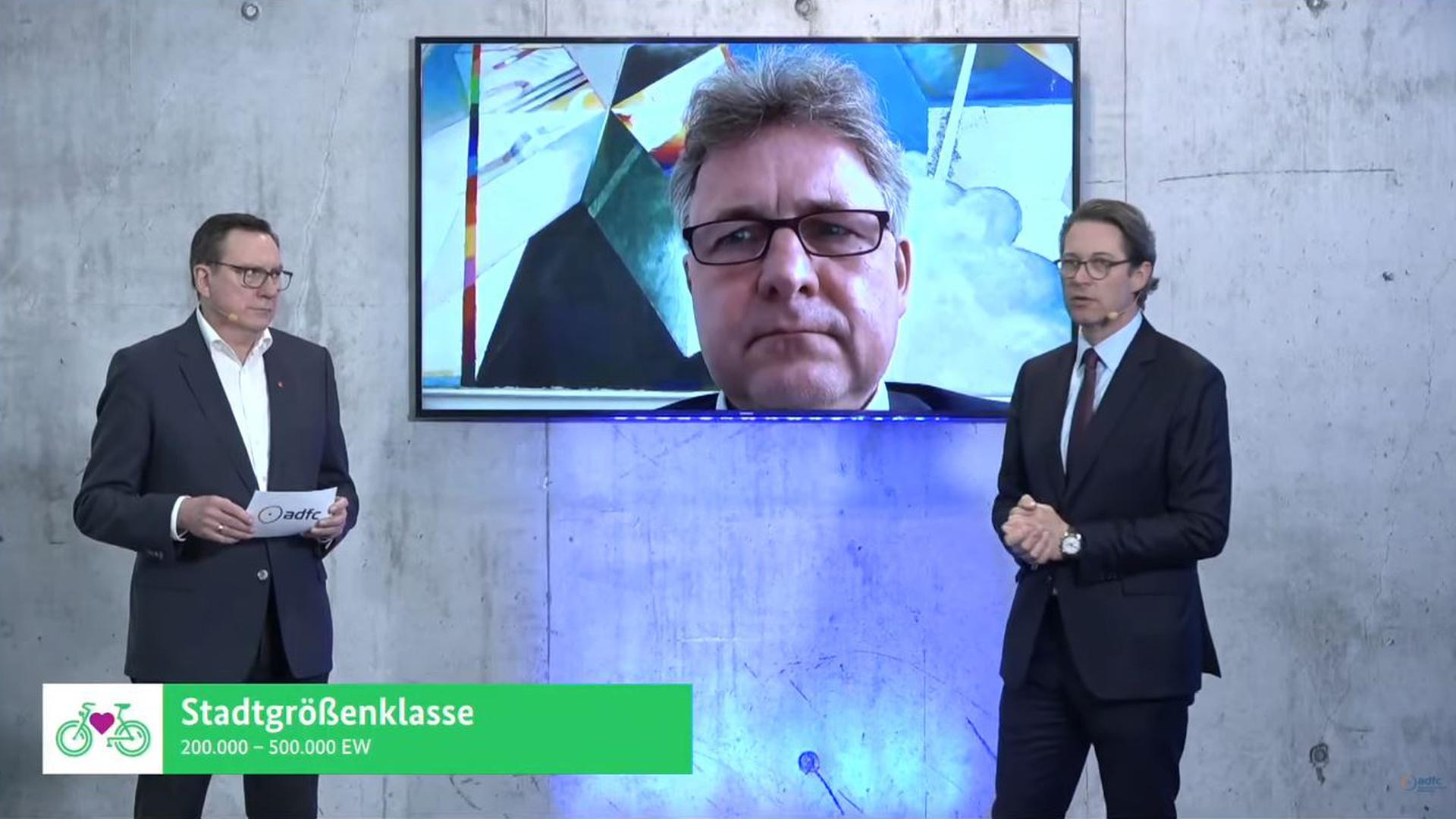 Der Karlsruher Oberbürgermeister Frank Mentrup (Mitte) hat per Live-Stream die Auszeichnung als fahrradfreundlichste Großstadt von Bundesverkehrsminister Andreas Scheuer (rechts) entgegengenommen.