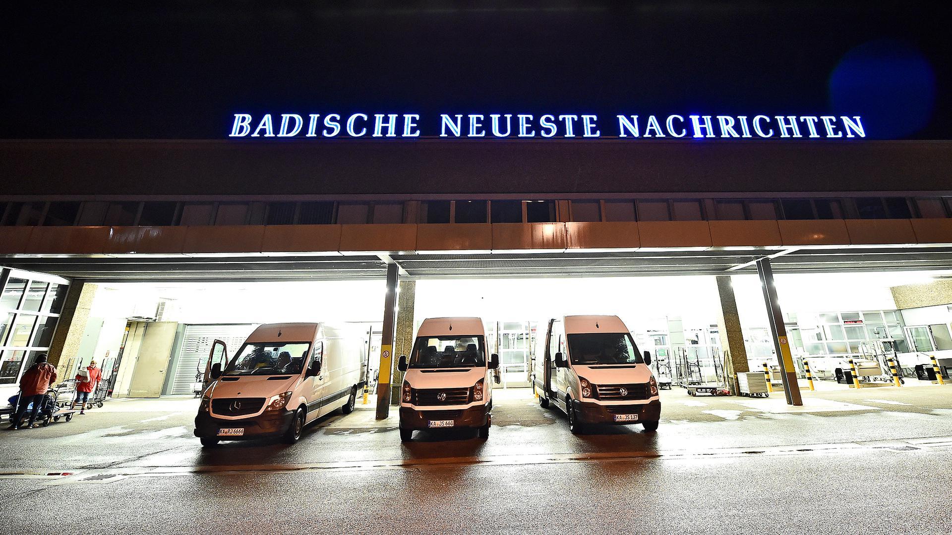Weiße Lieferwagen parken vor der hell erleuchteten Druckerei der Badischen Neuesten Nachrichten. Sie warten auf die fertigen Zeitungen.