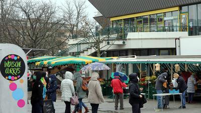 Menschen kaufen bei Regen auf dem Wochenmarkt in Neureut ein.