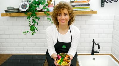 Angelique Sapnara sitzt mit einer kalten Bowl in der Hand in ihrer Küche.