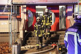Einsatzkräfte der Feuerwehr verlassen ein Schulgebäude.