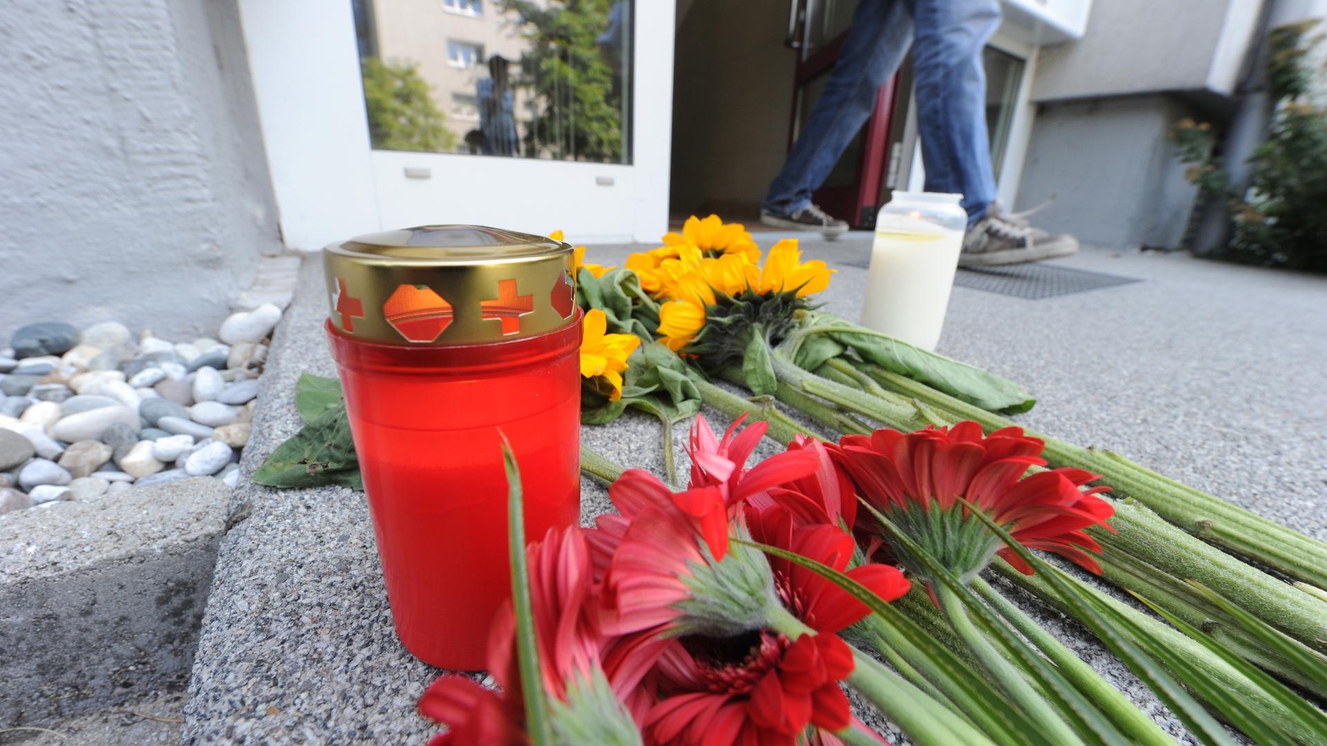 Vor einem Hauseingang im Stadtteil Nordstadt in Karlsruhe liegen am Donnerstag (05.07.2012) Blumen. Bei einer Zwangsräumung in dem Haus ist es am Mittwoch (04.07.2012) zu einer Schießerei mit einer Geiselnahme gekommen. Dabei hat es fünf Tote gegeben. Foto: Uli Deck dpa/lsw ++ +++ dpa-Bildfunk +++