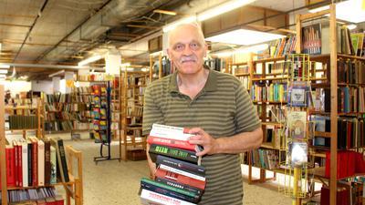 Thomas Stieber steht mit einem Bücherstapel auf dem Arm vor Bücherregalen