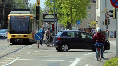 Fahrradfahrer, eine S-Bahn und ein Auto am Karl-Wilhelm-Platz in Karlsruhe.
