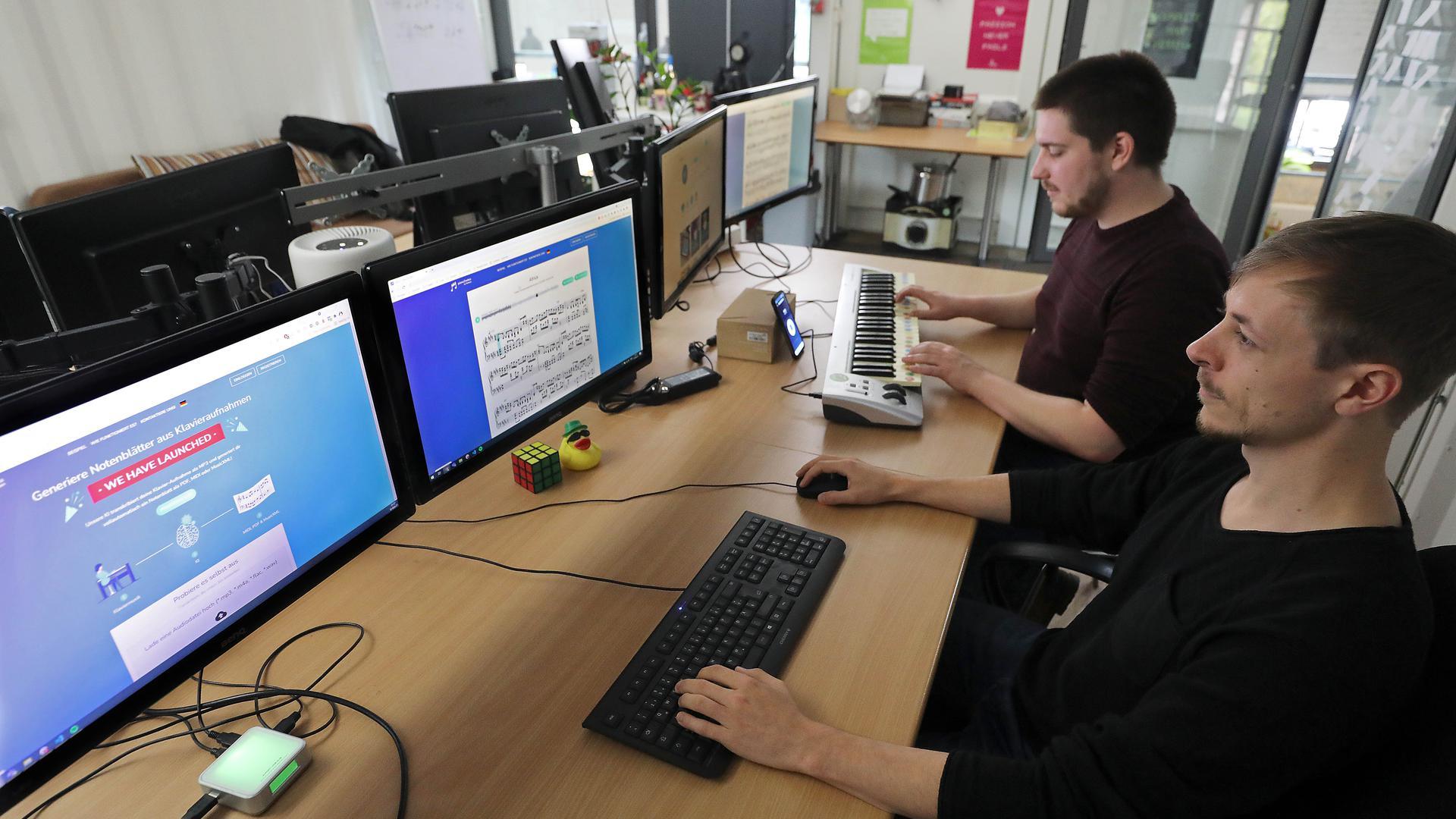 Der Elektrotechniker Sebastian Murgul (hinten) und der Informatiker Alexander Lüngen haben ein digitales Programm mit künstlicher Intelligenz entwickelt, das zu einem Song das Notenblatt schreibt.