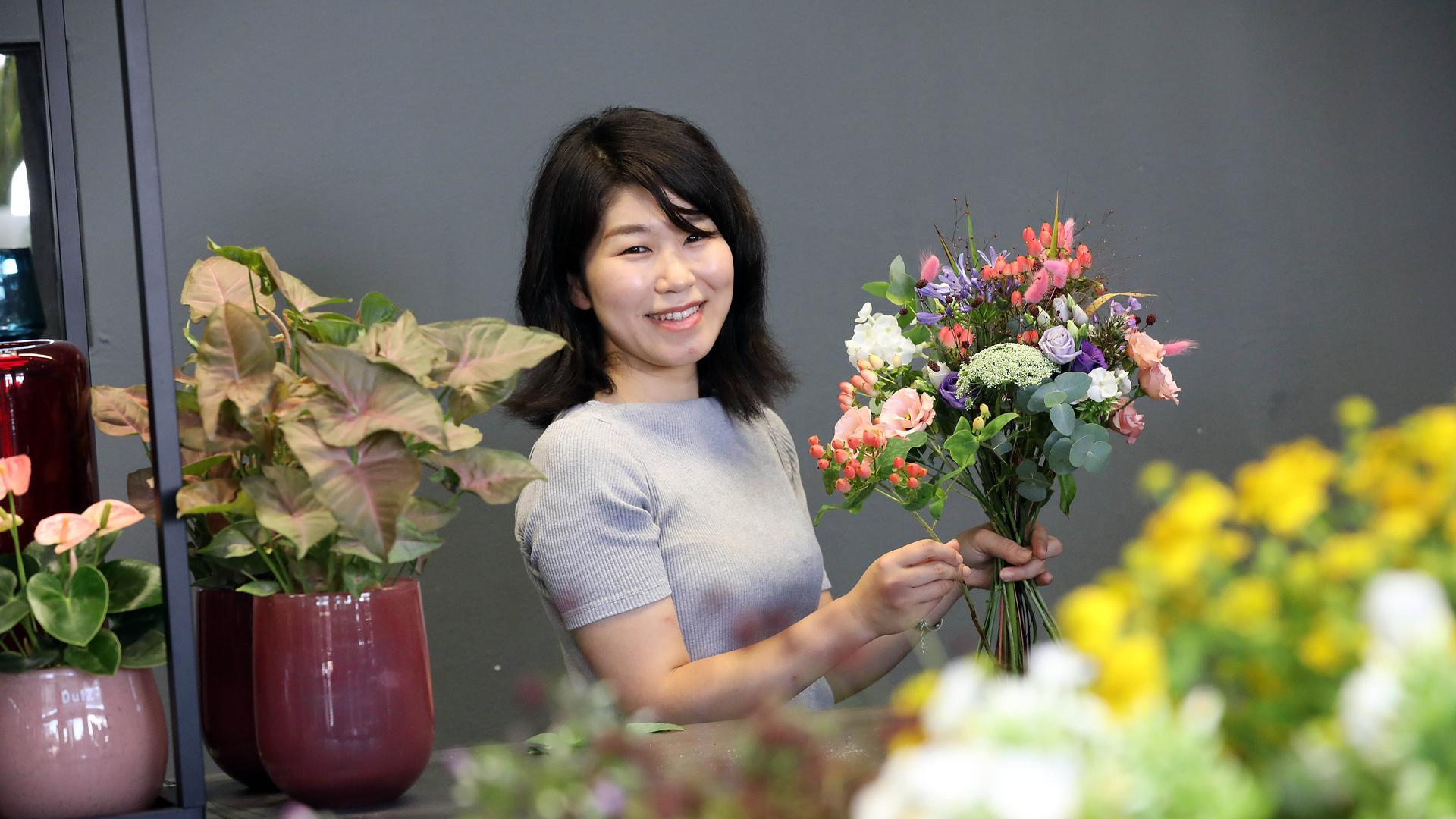 Haruka Maekawa bindet einen Strauß Blumen und achtet akribisch darauf, dass alle Farben zur Geltung kommen.