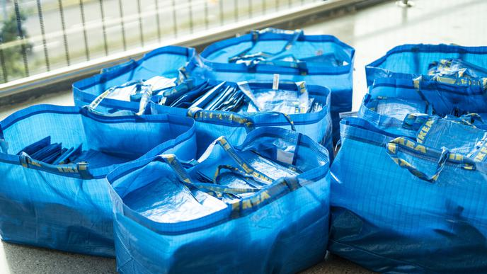 Die typischen blauen IKEA-Taschen liegen im Eingangsbereich für die Besucher der Eröffnung bereit.