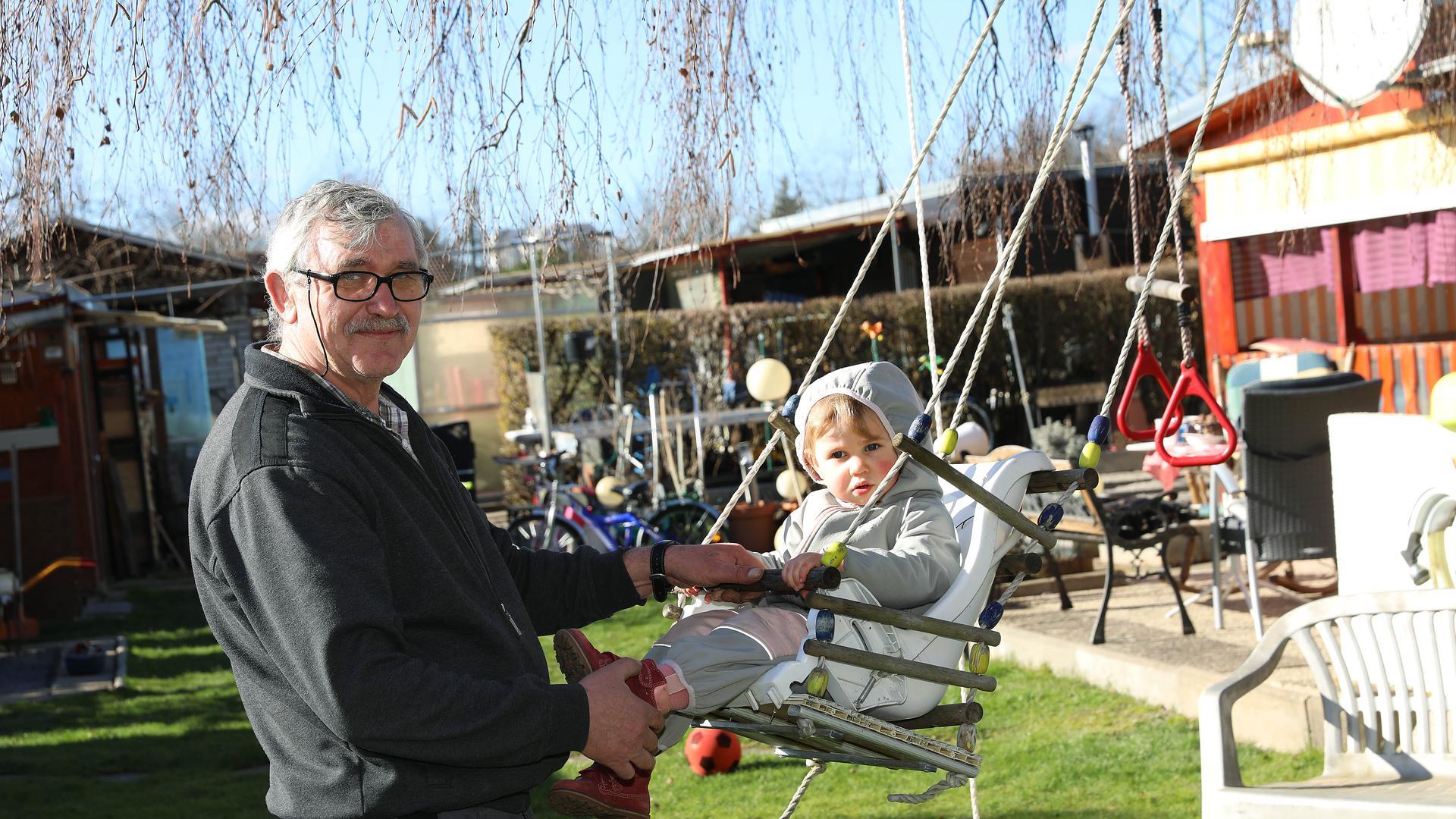 Sergej Stoll schubst seine Enkelin Viktoria in der Schaukel an.