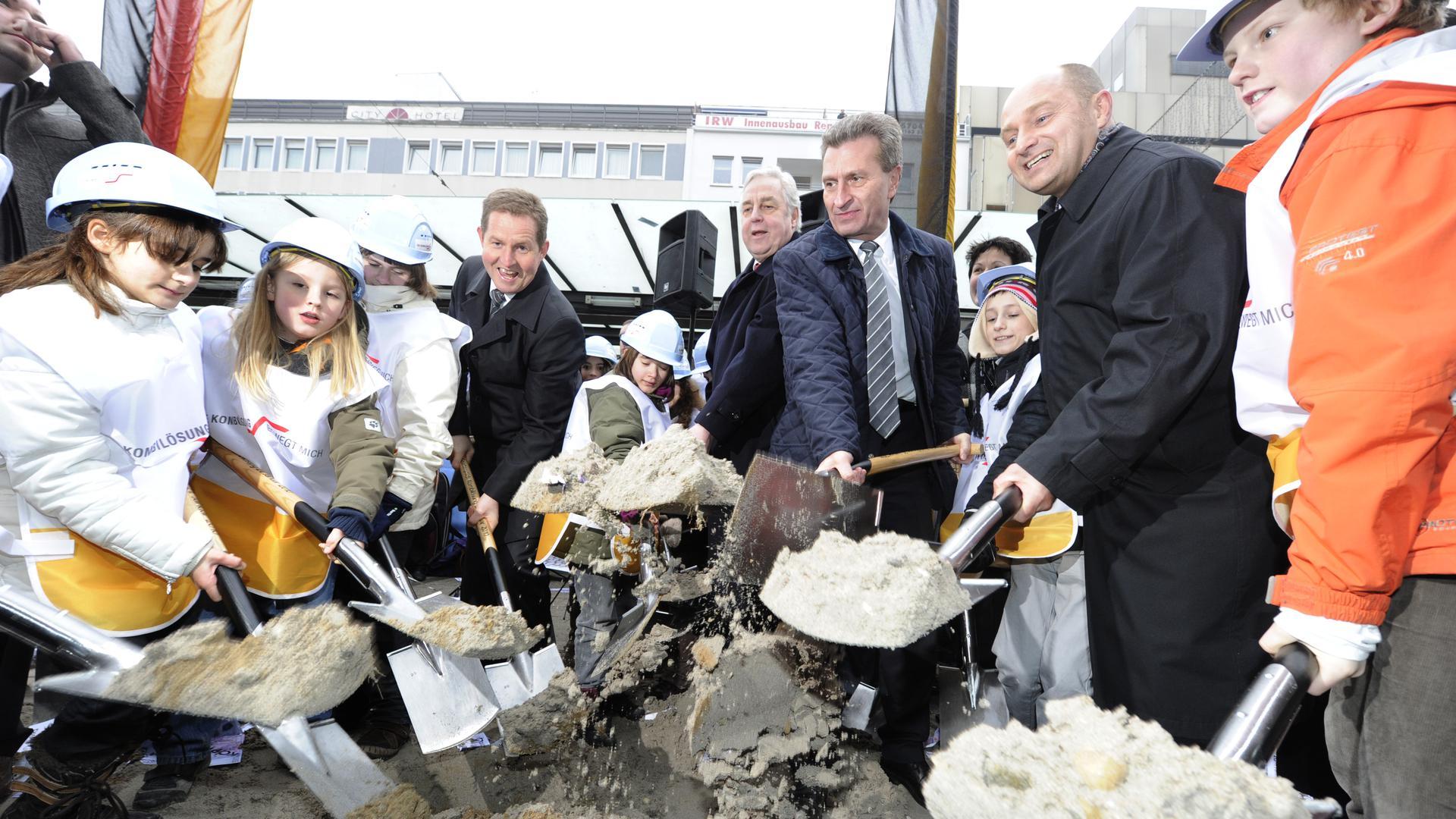 Schüler sowie Walter Casazza, Heinz Fenrich, Günther Oettinger und Rainer Bomba halten beim Spatenstich für die Kombilösung Karlsruhe Schaufeln in der Hand.