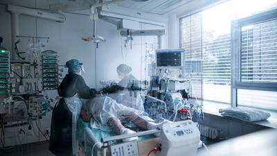 Krankenpflegerinnen in Schutzausrüstung betreuen einen Corona-Patienten.