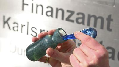 """Vor dem Finanzamt Karlsruhe Stadt wird ein Flacon mit dem Parfüm """"Aerarium"""" gezeigt."""
