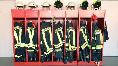 Ein Schrank mit Jacken und Helmen einer Freiwilligen Feuerwehr.