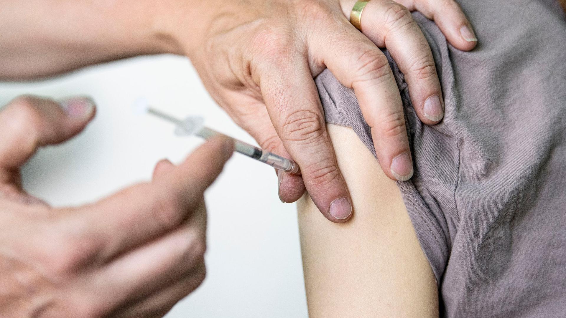 Ein Kinder- und Jugendarzt impft eine junge Frau mit dem Corona-Impfstoff Comirnaty von Biontech/Pfizer.