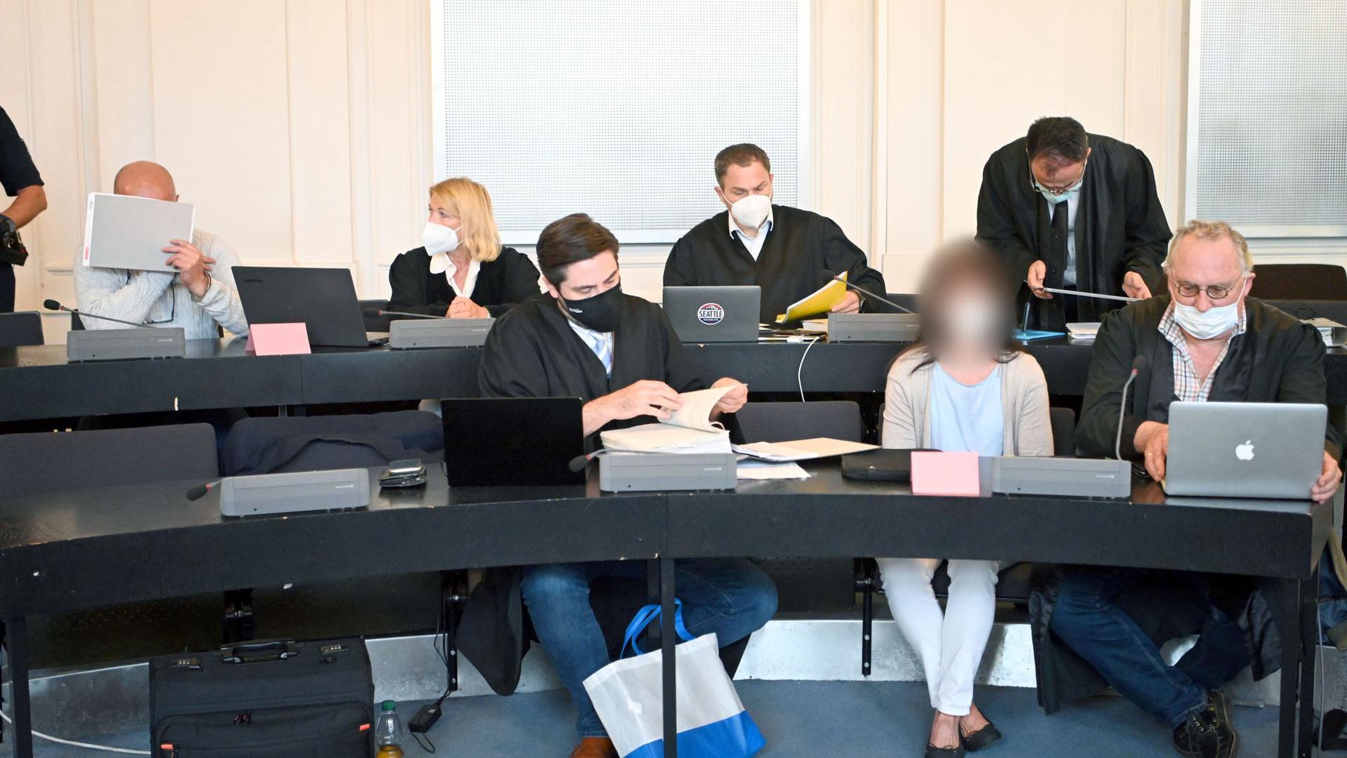 Ein 43 Jahre alter Angeklagter (l) und eine 49 Jahre alte Angeklagte (5.v.l. vorne) mit ihren Anwälten.