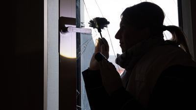 Eine Kriminaloberkommissarin sichert Spuren an einer eingeschlagenen Fensterscheibe.