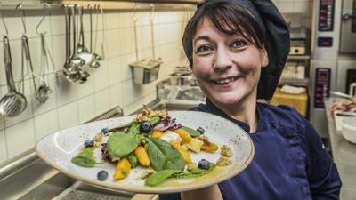 Köchin Tanja Finck hält einen Teller mit Kürbis-Schupfnudeln in der Hand.