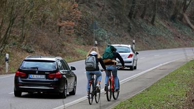 Fahrradfahrer fahren auf einem schmalen Radweg direkt neben der Straße.