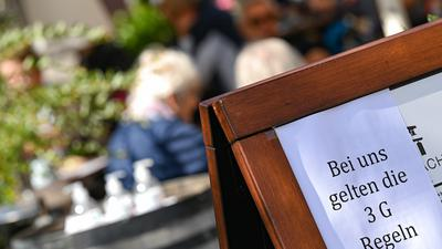 Vor dem Café Hauptwache in der Frankfurter Innenstadt ist eine Tafel mit der Aufschrift «Bei uns gelten die 3 G Regeln» aufgestellt. Rund eine Woche nach dem Start des 2G-Optionsmodells bei den hessischen Corona-Regeln ziehen Gastgewerbe und Friseure ein durchweg positives Resümee. (zu dpa «2G-Regeln: Gastgewerbe und Friseure sehen neue Vorgaben positiv») +++ dpa-Bildfunk +++