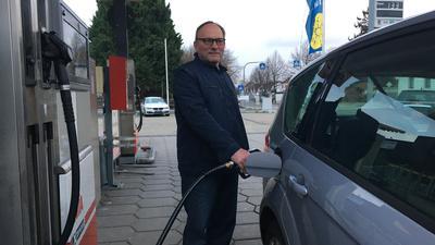 Ein Mann betankt sein Auto