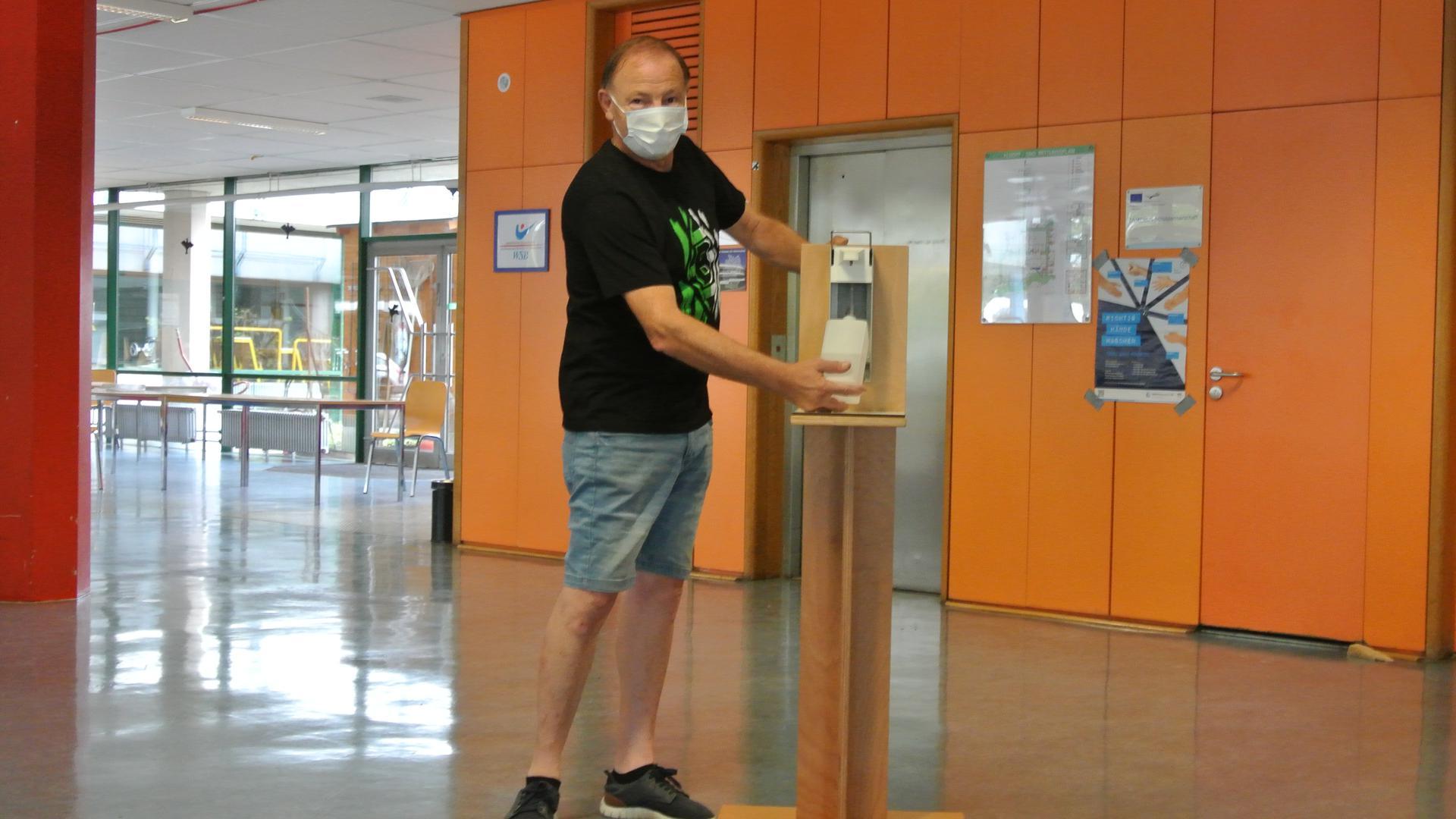 Ein Mann mit Maske steht neben einem Desinfektionsmittel-Spender