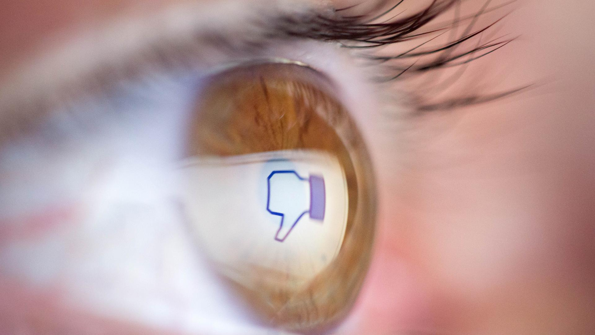 Großaufnahme eines menschlichen Auges mit brauner Iris. In der Pupille spiegelt sich das Icon eines nach unten zeigenden Daumens im Facebook-Design.