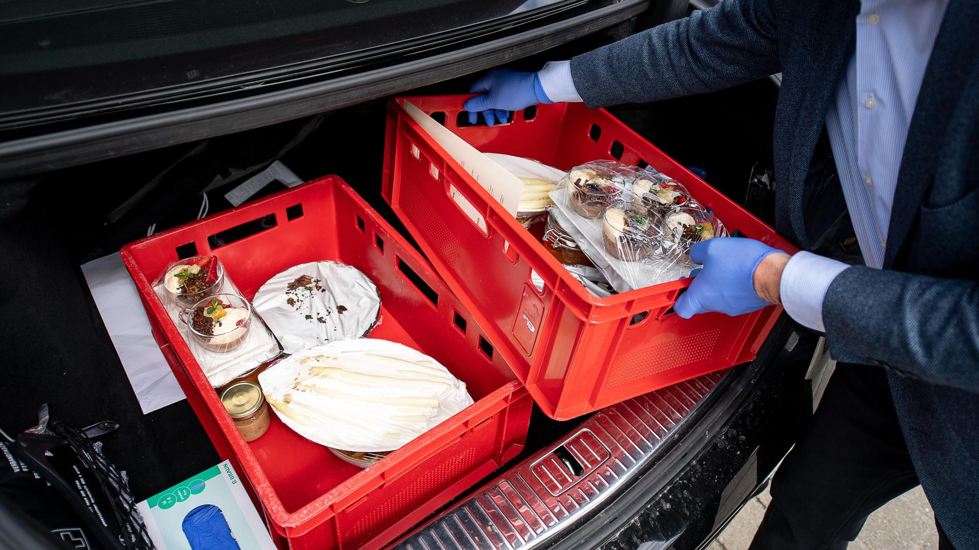 Ein Mann lädt zwei Kisten mit Essen in seinen Kofferraum.