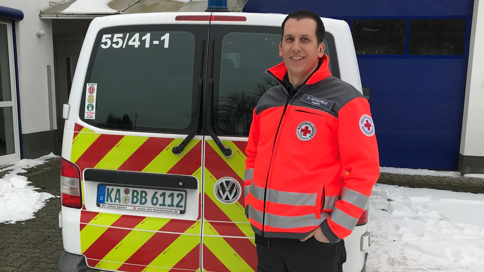 Ehrenamtlicher beim Deutschen Roten Kreuz, Daniel Mitschele, vor der Wache in Blankenloch. Ein Einsatzfahrzeug im Hintergrund.