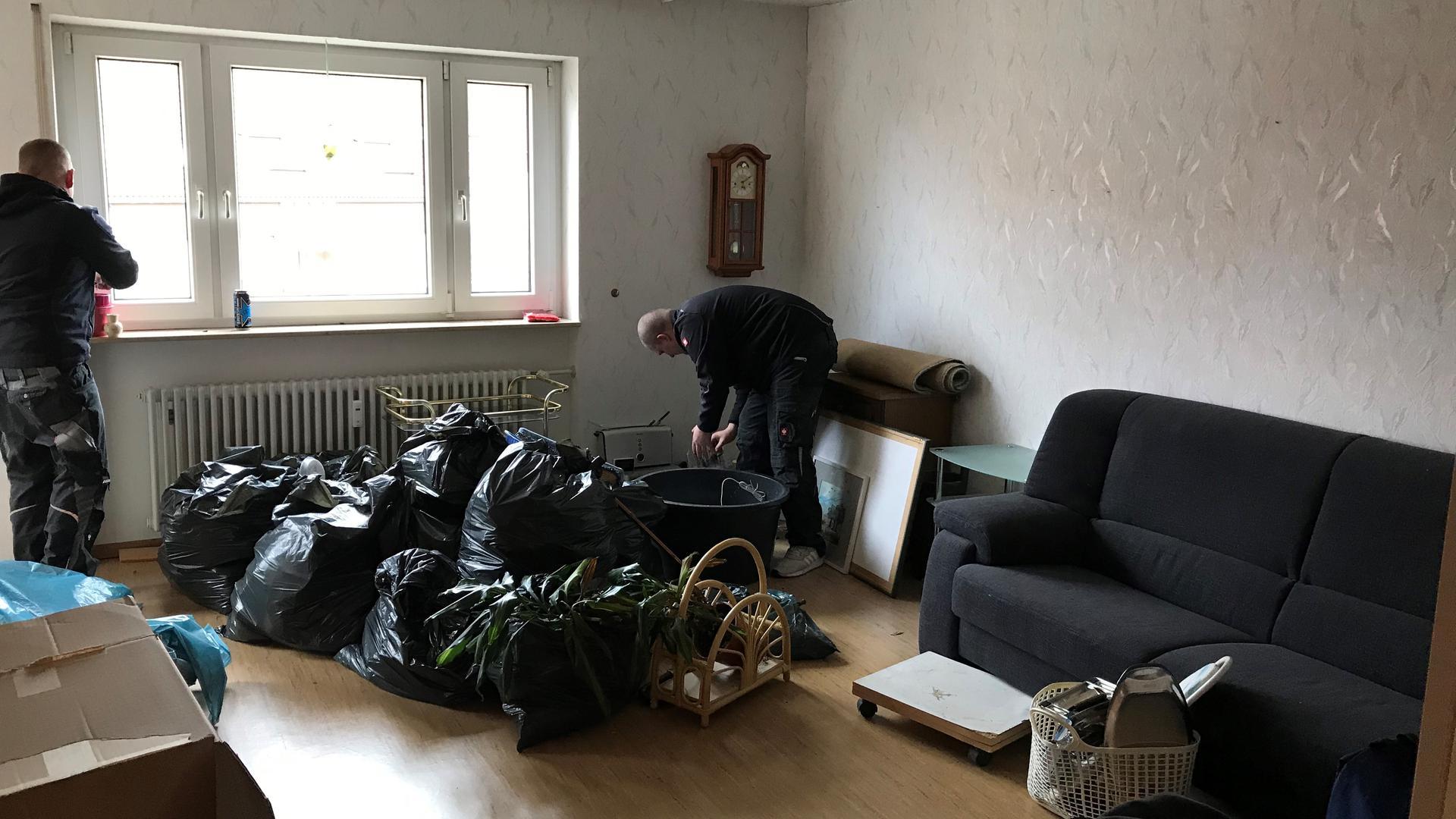 Wohnzimmer mit schwarzen Plastiksäcken in der Mitte