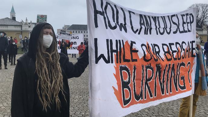 """""""How can you sleep while our beds are burning?"""" steht auf einem Banner bei der Demo von Fridays For Future."""