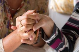 Eine Therapeutin  hält in einem Hospiz die Hand einer todkranken Bewohnerin.